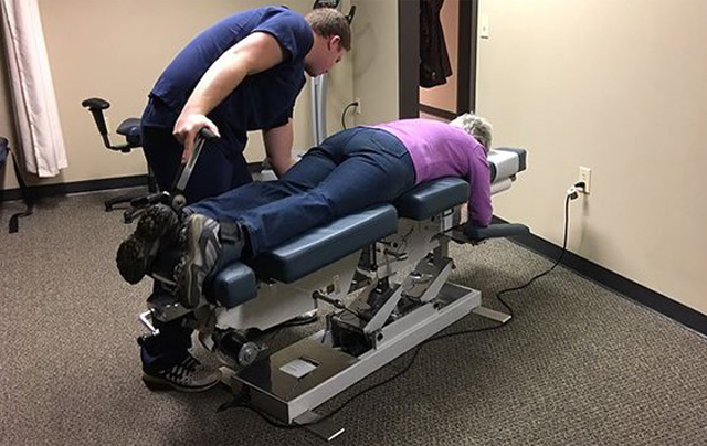 chiropractor with patient lying on adjusting table